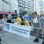 People carry the ADA 25 banner as they march.