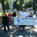 Person carries banner for Independent Living Center of the North Shore and Cape Ann, Inc.
