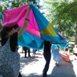 People carry a colorful banner over their heads.