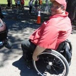 Person in red shirt smiles seated in a wheelchair.