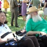 Two people in wheelchairs smile in the shade of some trees.