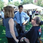 Person in wheelchair and person in a striped shirt speak with a person in a blue shirt and tie.