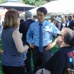 Person in a wheelchair and a person in a striped shirt speak with a person in a blue shirt and tie.