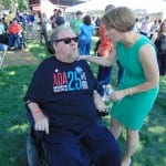 A person in a green dress speaks with a person wearing a black ADA 25 t-shirt seated in a wheelchair.