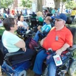 A group of people in wheelchairs converse in the shade of some trees.
