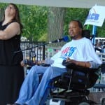 A person in a wheelchair speaks into a microphone while an interpreter uses ASL to their right.
