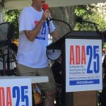 A person holds a red microphone and addresses the crowd. Sign on the podium reads ADA 25 years. Celebrate the Americans with Disabilities Act. Boston Common July 22, 2015 #ADA25Boston