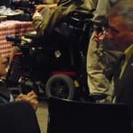 A person in a suit speaks to a person in a wheelchair.