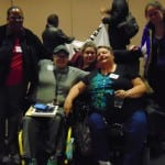 Two people stand behind three people in a wheelchair and take a photo before the meeting.