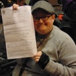 A person in a wheelchair holds up a piece of paper.