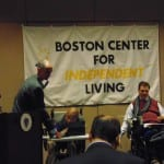 Two people are seated in wheelchairs while a BCIL staff member holds a microphone.