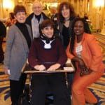 A person in a wheelchair and four other people get together for a photo.