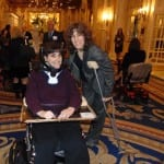 A person in a wheelchair and a person on crutches smile for a photo.