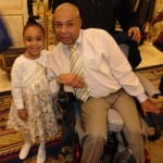 A person seated in a wheelchair takes a photo next to a child in a white dress.