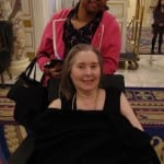 A pair of guests, one in a wheelchair, smile for a picture.