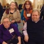Four guests take a picture, two people in wheelchairs.