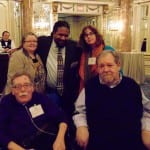 A BCIL staff member takes a picture with four guests, two people in wheelchairs.