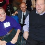 A BCIL staff member takes a picture with two people in wheelchairs.