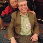 Two people, one in a wheelchair, smile for a picture.