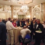 Attendees in the ballroom conversing over refreshments.