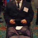 A person in a wheelchair has his photo taken.
