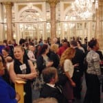 Attendees seated in the ballroom conversing over refreshments.