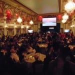 Attendees seated at tables in the ballroom. A projector screen is open at the front of the room.