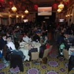 Attendees seated in the ballroom. A projector screen is open at the front of the room.