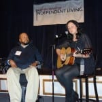 Person seated in wheelchair sits next to seated person strumming a guitar.