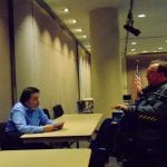 Person in blue shirt speaks at table to a person in a wheelchair.