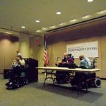 Person in wheelchair is talking into a microphone while two people in wheelchairs are situated at a table.