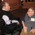 Two people in wheelchairs talk in the ballroom.