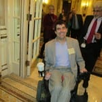 Person in wheelchair wearing a gray suit smiles for a photo.