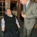 A person with a drink in their hand speaks with a person in a wheelchair.