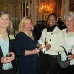 Four guests smile for a photo as they hold drinks.