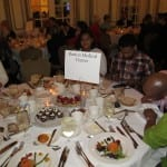 Attendees have dinner at the event. The sign on the table reads Boston Medical Center.
