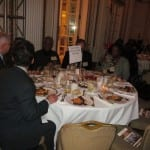 Attendees converse over dinner at a table.