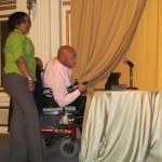 A person in wheelchair is talking into a microphone while a person in a green blouse stands next to them.