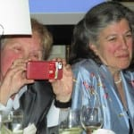 Person at table holds up red camera phone to take picture.