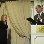 Speaker at podium presents honoree award.