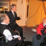 A person in a dark blue suit speaks to two people in wheelchairs.