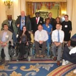 Seven people stand behind five people in wheelchairs for a group photo.