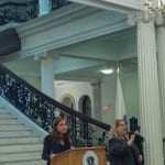 A person speaks at the podium in front of the State House's main staircase with an ASL interpreter to the left.