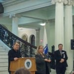A person speaks at the podium in front of the State House's main staircase with two people standing to the left of the podium.