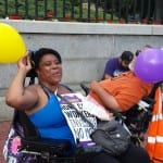 A person in a wheelchair cheers and throws her fist in the air.
