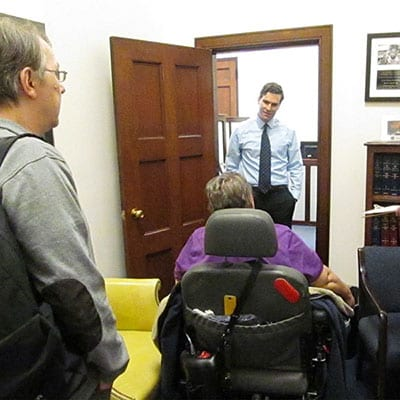 A person in a wheelchair visits the office of legislator.