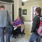 A person in a wheelchair waits for an elevator to arrive.