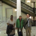 Three people take a group photo in the lobby of the State House.