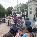A speaker addresses the crowd outside the State House.