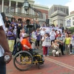 A person in in a wheelchair speaks to a crowd through a microphone outside the State House.